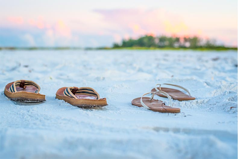A pair of men's and women's sandals on a white sand beach at sunset