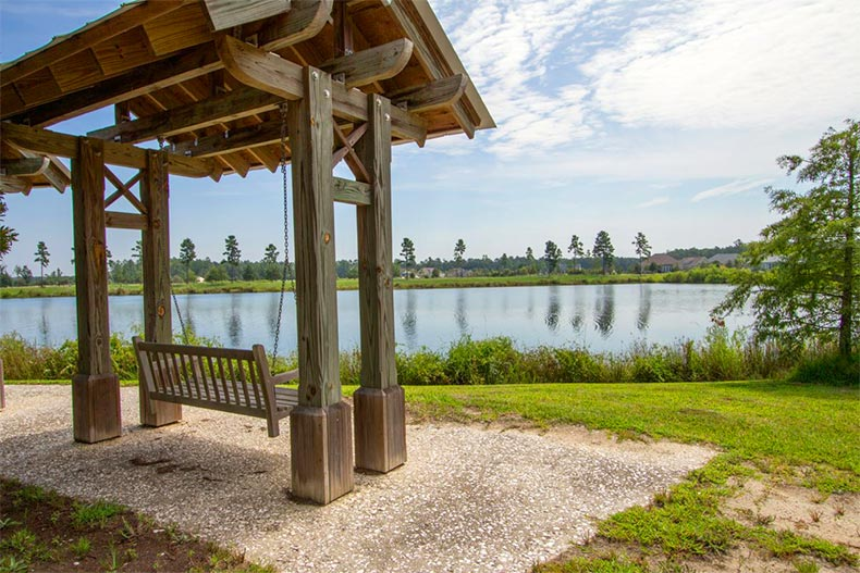 A wooden swing beside a picturesque pond at Hilton Head Lakes in Hardeeville, South Carolina
