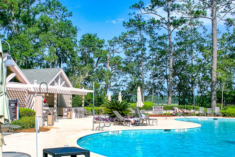 Pool, patio, and clubhouse with trees in the background in Sun City Hilton Head, SC