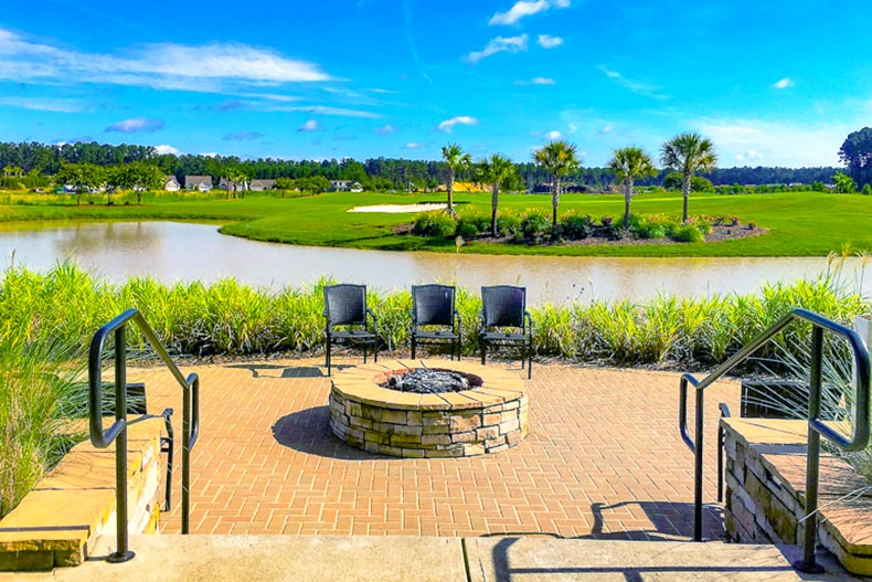 fire pit and chairs in front of lake in Sun City Hilton Head