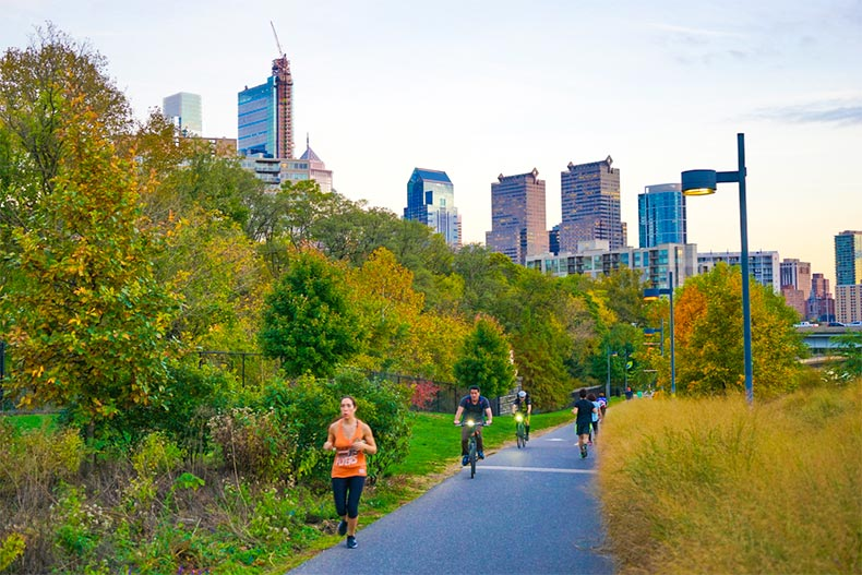 Eventing runners and cyclists on the Schuylkill River Trail with Philadelphia skyline