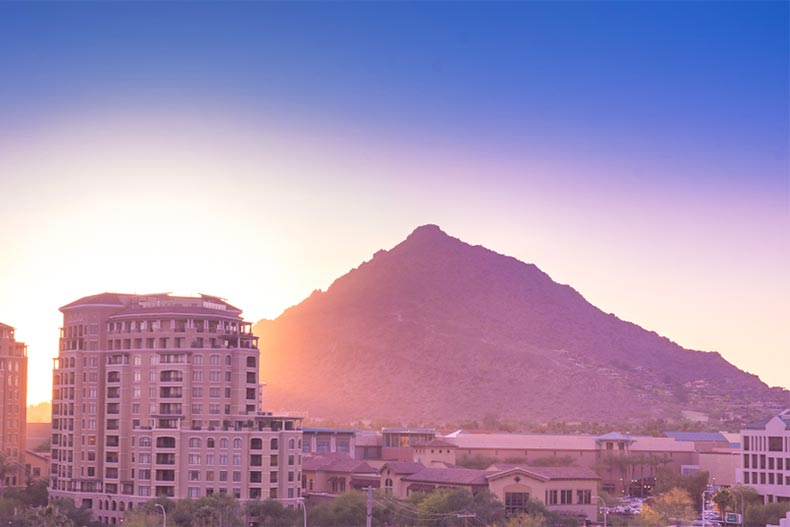 Sunset blocked by a high-rise condo building in Scottsdale. Large mountain looms behind