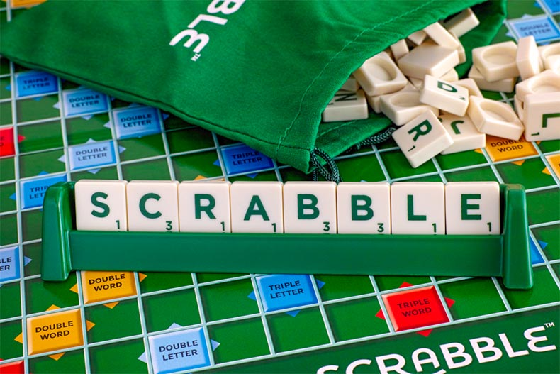 Close up on a board of Scrabble with tile pieces spelling Scrabble