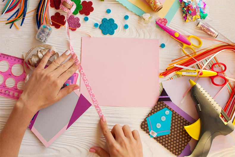 Person scrapbooking with glue gun and other materials nearby