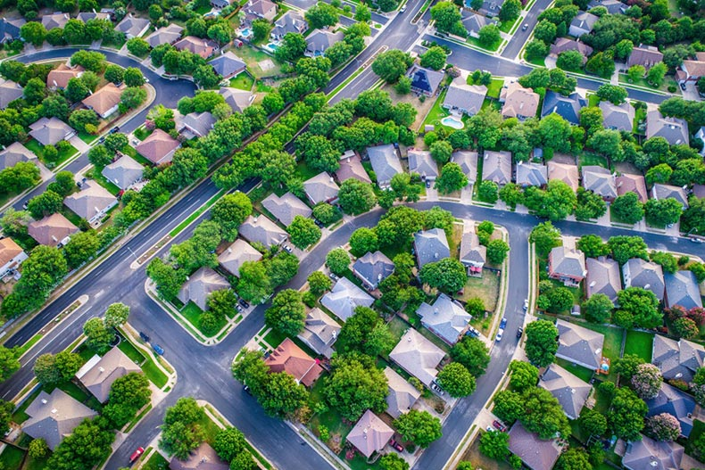 An aerial view of a suburban neighborhood in the summertime