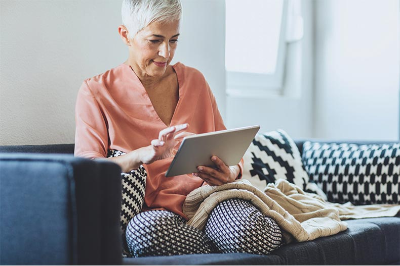 Older woman sitting comfortably on couch looking at tablet