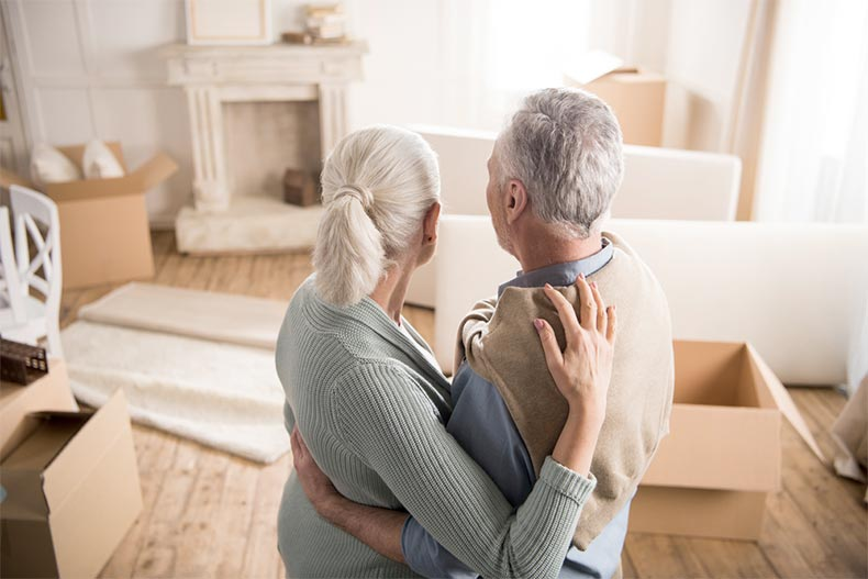 An older couple holding each other as they look at the moving boxes in their living room