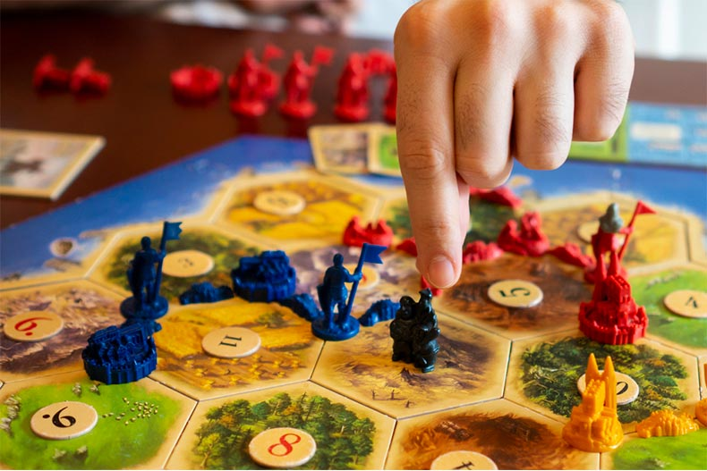 Close up of person playing Settlers of Catan