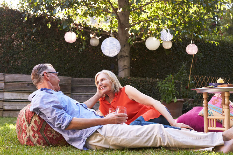 older couple sitting on pillows in the backyard with drinks