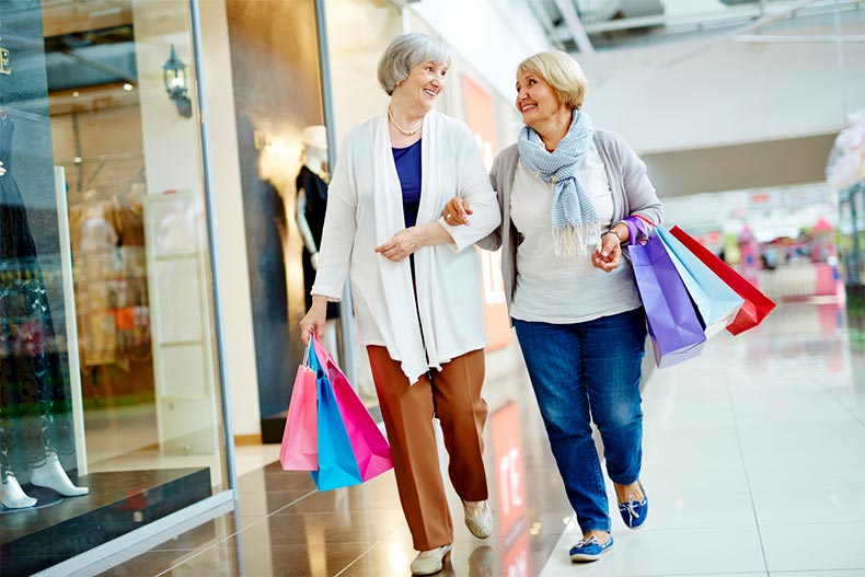 Active adult ladies shopping in a mall while carrying colorful shopping bags