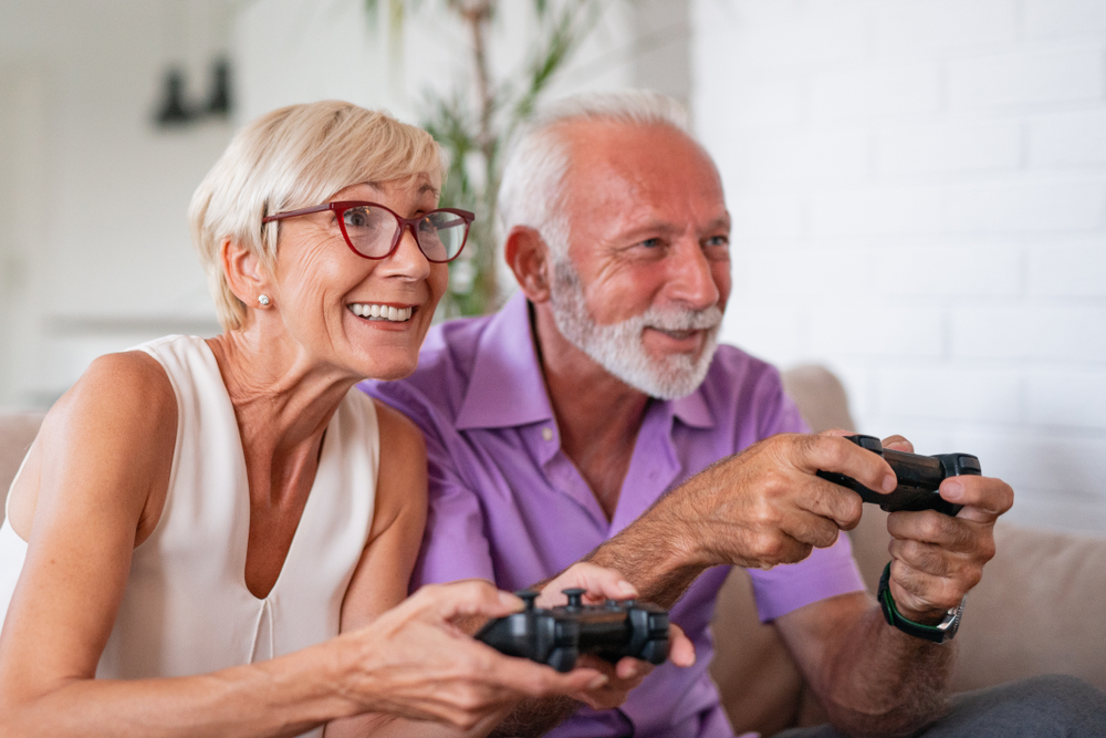 An older couple smiling and having fun while playing video games
