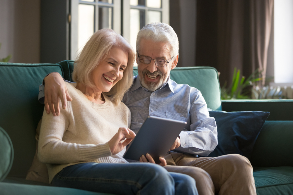 An older couple smiling while sitting on a couch and playing a game on a tablet