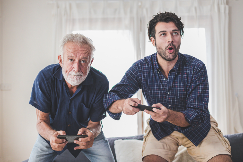 An older man and his adult son getting competitive while playing video games on their smart phones
