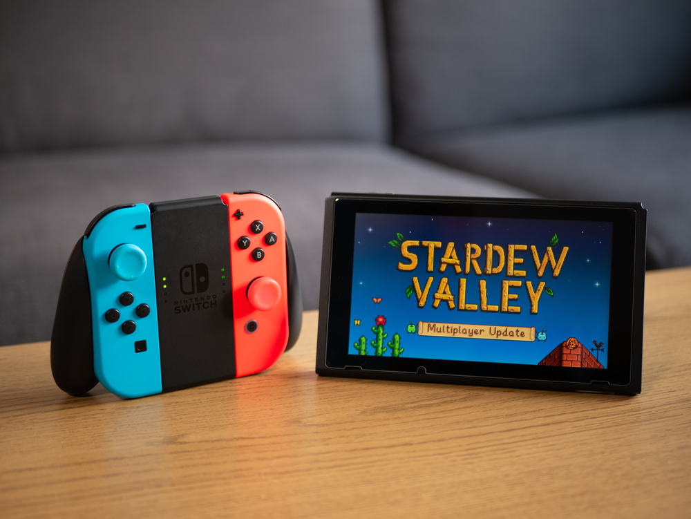 "A Nintendo Switch on a coffee table displaying ""Stardew Valley"" on the screen"