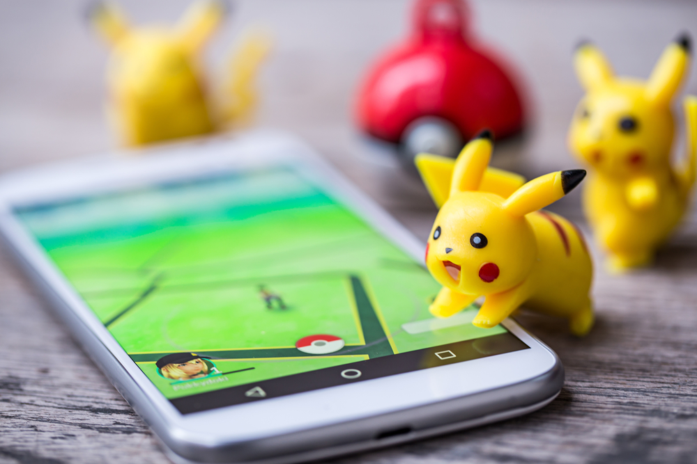 "Three plastic Pikachus and a plastic poke ball surrounding a smart phone displaying ""Pokemon Go"""