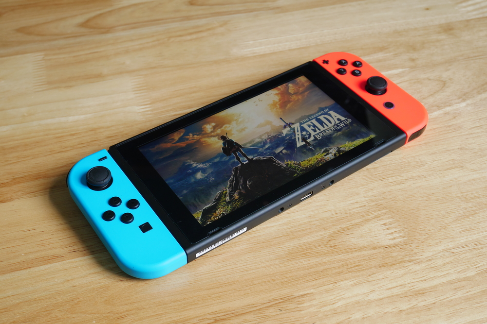 "A Nintendo Switch sitting on a wood surface and displaying ""The Legend of Zelda: Breath of the Wild"""