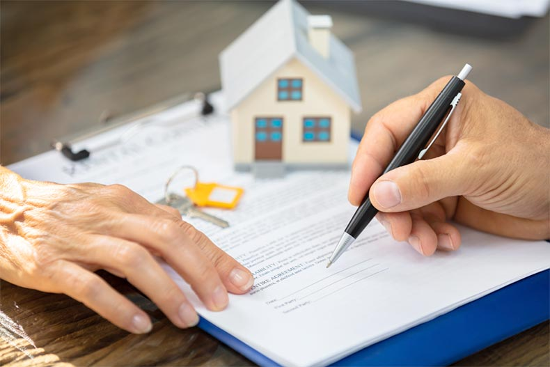 Close-up of a real estate agent's hand helping a client sign a deed