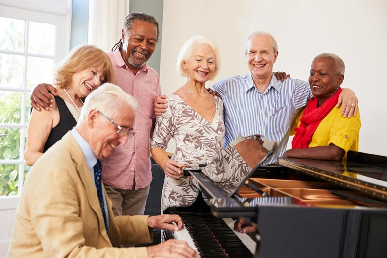 Group of older adults singing around a piano