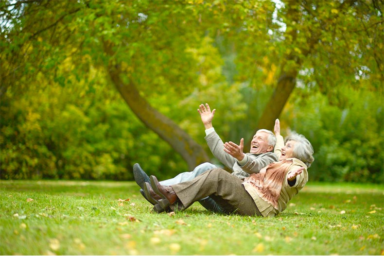 Older couple laughing in a park