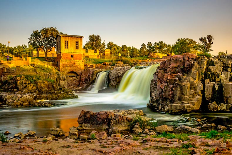 Sunset view of a several buildings near a waterfall in Sioux Falls, South Dakota