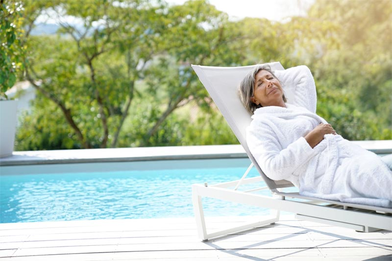 active adult senior relaxing in sunshine by pool