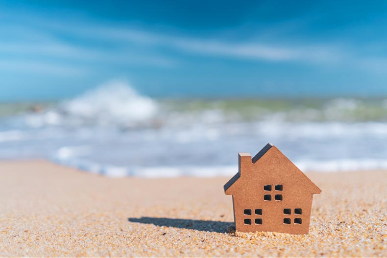 A small wooden house silhouette on a beach with a blue sky and white clouds in the background