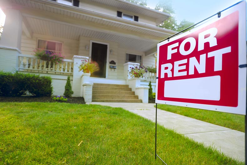"A ""For Rent"" sign in front of a picturesque snowbird property"