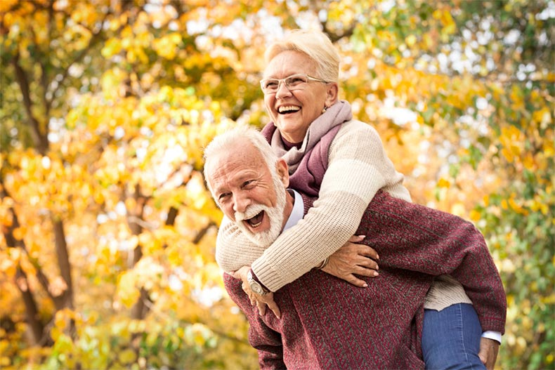 A happy older couple laughing and having fun in an autumn park