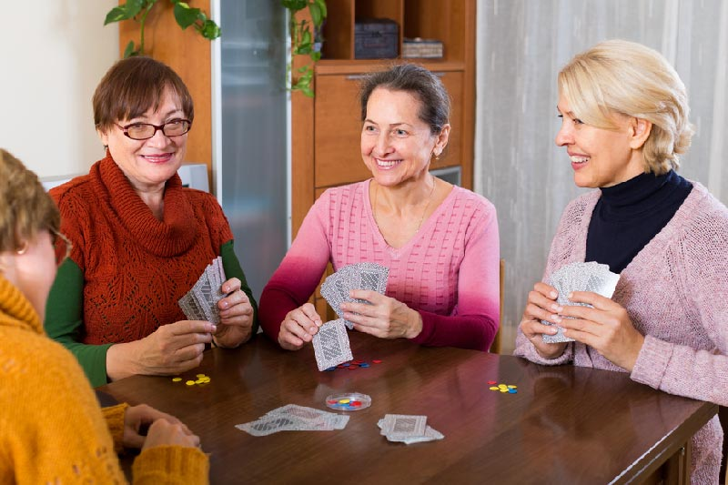 group of seniors laughing and playing cards in community