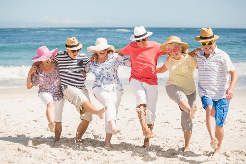 A group of senior friends laughing and dancing on a beach on a sunny day