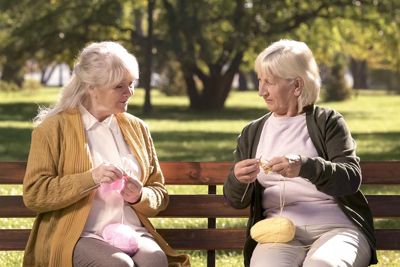 Two older women sitting on a park bench in the summertime and crocheting together