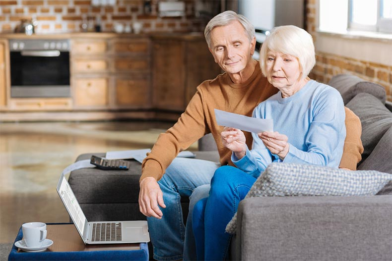 An older woman sitting with her husband while looking over a Social Security document