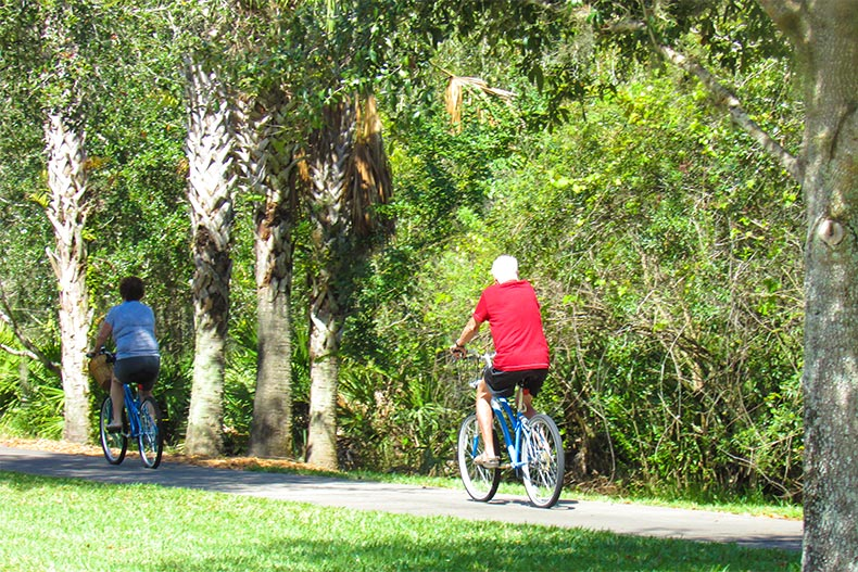 A senior couple biking on a trail in Solivita