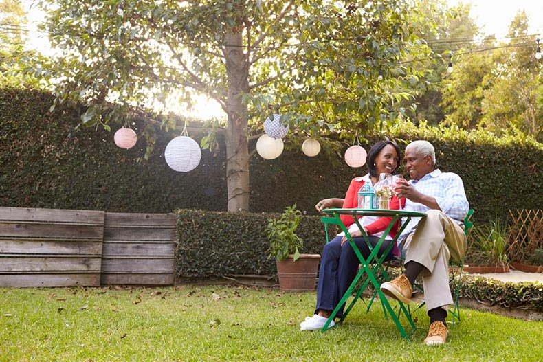 A senior couple lounging at a table in their backyard and enjoying drinks on a sunny day