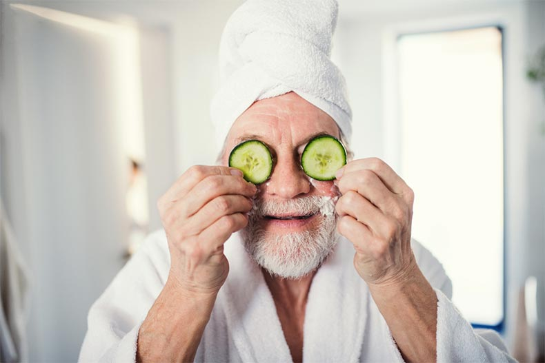 A senior man in a bathrobe with cucumber slices in front of his eyes