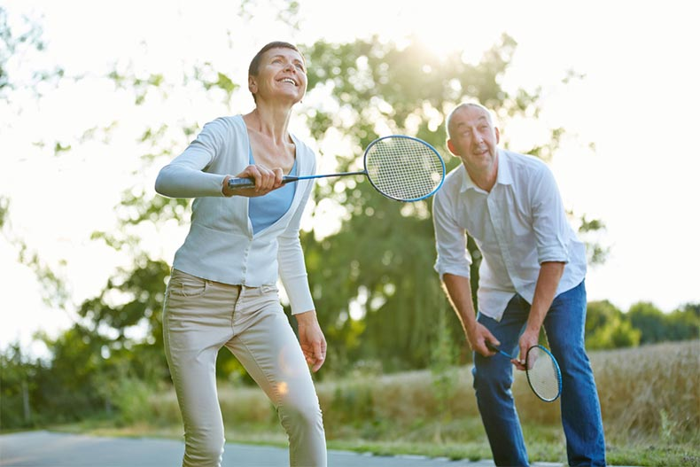 A senior couple in casual clothes playing badminton outside