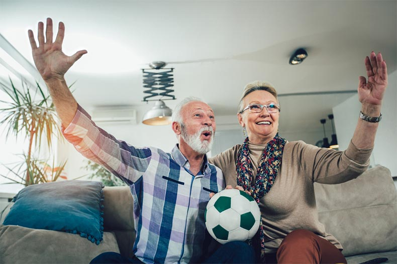 A happy senior couple watching soccer on tv and celebrating a goal at home