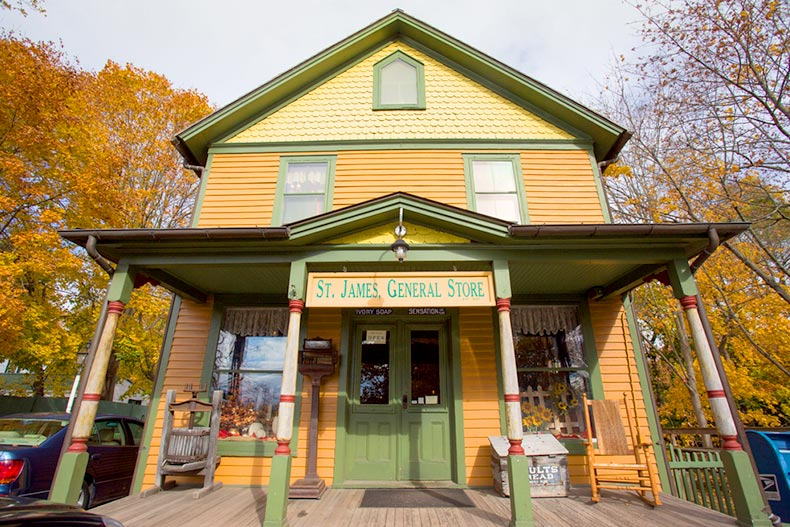 St. James General Store, a green and orange house in Suffolk County, Long Island with autumn trees in the background