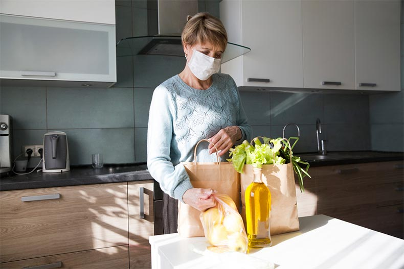 Seniors woman wearing a medical face mask while unpacking groceries