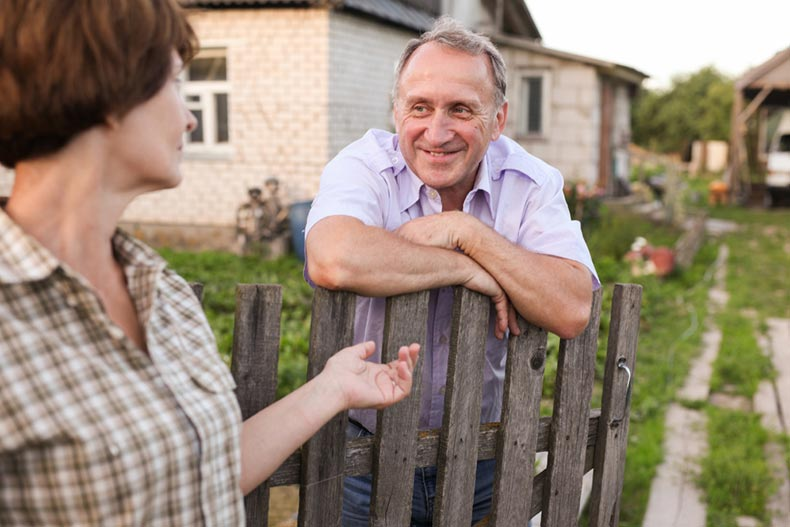 An active adult woman talking to her neighbor over a fence