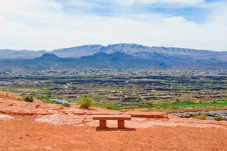 Aerial view of the St. George, Utah from a nearby hiking trail. Adobe bench in the foreground, mountain ranges in the background