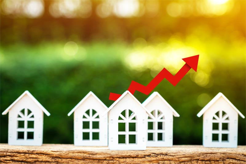 illustration of homes with stock arrow in the background going in an upward trend