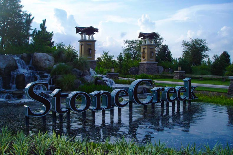 View of the community sign and entrance gate surrounded by well-manicured landscaping at Stone Creek in Ocala, Florida