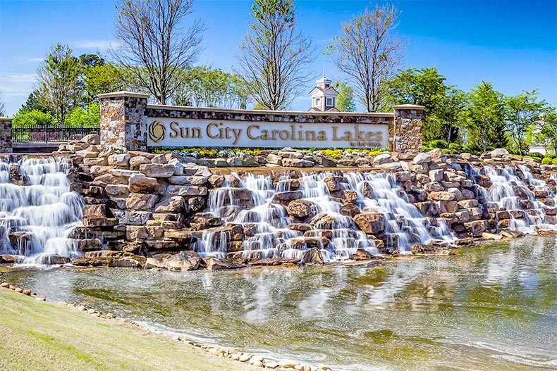 A blue sky over the sign for Sun City Carolina Lakes atop a small man-made waterfall in Fort Mill, South Carolina