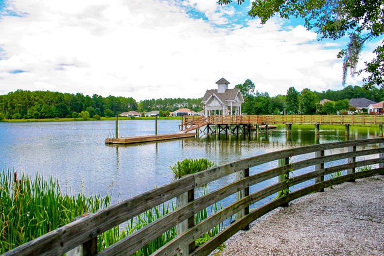 View from a walking trail of a picturesque lake with a dock at Sun City Hilton Head in Bluffton, South Carolina