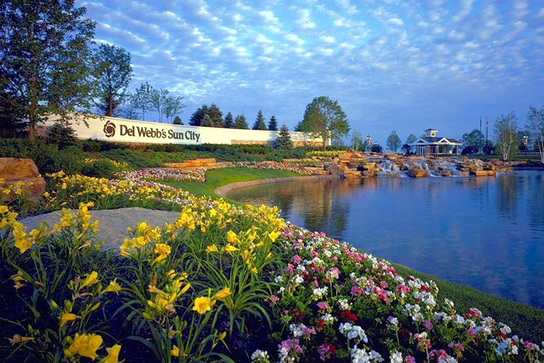Picturesque view of the water and flowers surrounding the community sign for Sun City Huntley in Huntley, Illinois