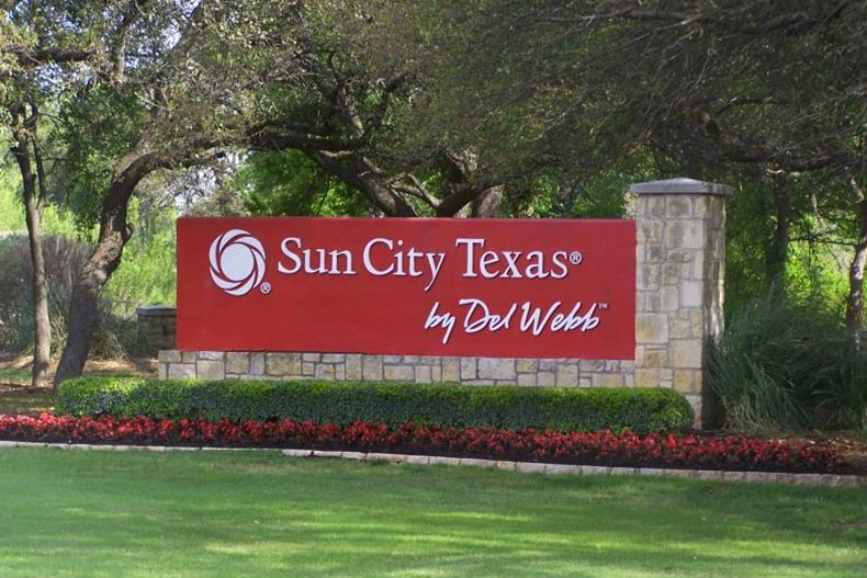 Greenery surrounding the community sign for Sun City Texas in Georgetown, Texas