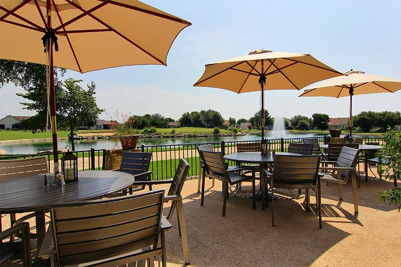 Tables and chairs on a patio overlooking a picturesque pond at Sun City Texas in Georgetown, Texas