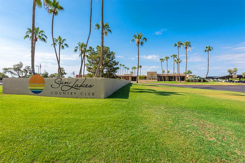 Palm trees and green grass surrounding the community sign for Sun Lakes Country Club in Banning, California