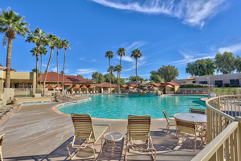 View of the outdoor pool and patio surrounded by palm trees at Sun Village in Surprise, Arizona